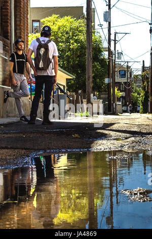 Two hipsters having a conversation on back alley in Lodo Denver - Stock Photo