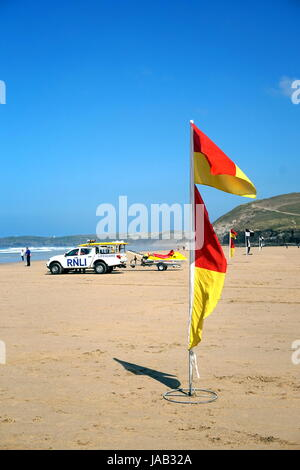 Newquay, Cornwall, UK - April 7 2017: Red and yellow lifeguard flags on the beach for swimmers and surfers, with - Stock Photo