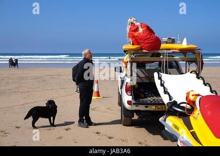 Newquay, Cornwall, UK - April 7 2017: Female RNLI lifeguard talking to a man with a dog on a surfing beach in Newquay - Stock Photo