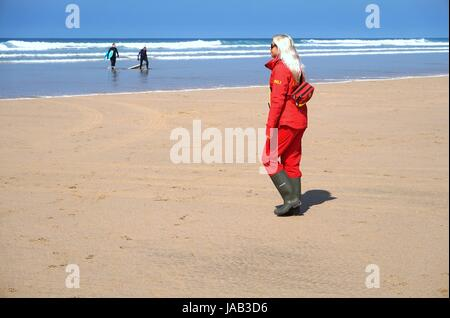 Newquay, Cornwall, UK - April 7 2017: Female RNLI lifeguard keeping watch on a surfing beach in Newquay - Stock Photo
