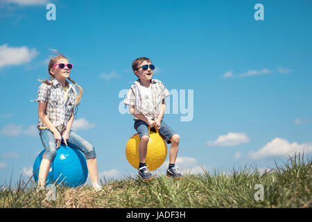 Brother and sister playing on the field at the day time. Children having fun outdoors. They jumping on inflatable - Stock Photo