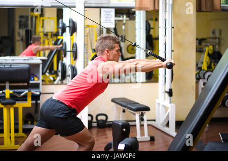 Young man training on gym equipment, pulling handle on cables - Stock Photo