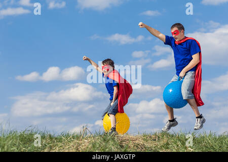 Father and son playing superhero at the day time. People having fun outdoors.They jumping on inflatable balls on - Stock Photo