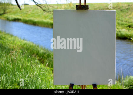 Blank painter artist canvas on wooden easel. Beautiful summer river landscape on background. Focus on foreground. - Stock Photo