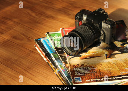 Close view of SLR camera and photography magazines - Stock Photo