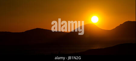 panoramic view of sunset over the Paps of Jura, as seen from Kintyre - Stock Photo