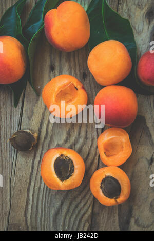Fresh ripe colorful apricots halved and whole on weathered plank wood background, kernel, green leaves, top view, - Stock Photo