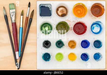 Artist paint brushes and palette with acrylic paint on wooden background - Stock Photo