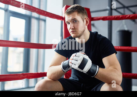 Portrait of young man posing in boxing ring sitting on floor and looking at camera looking at camera with confidence - Stock Photo