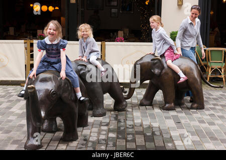 Children, kids, girls, ride and play upon the sculpture The Three Graces, by Philippa Downes, The sculptures theme - Stock Photo