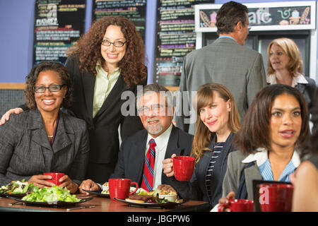 Smiling friends together for lunch in cafeteria - Stock Photo