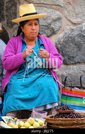 A woman in traditional dress knitting wool hats in the ...