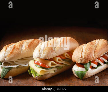 Trio of freshly baked golden vegetarian baguettes with a variety of cheese fillings with herbs and salad ingredients - Stock Photo