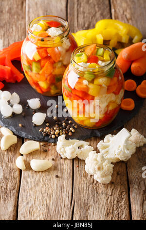 Italian Giardiniera salad of pickled cauliflower, pepper and carrots close-up in glass jars. Vertical - Stock Photo