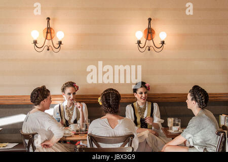 NOVI SAD, SERBIA - JUNE 11, 2017: Young women wearing a traditional Serbian costume having a drink in a local cafe - Stock Photo