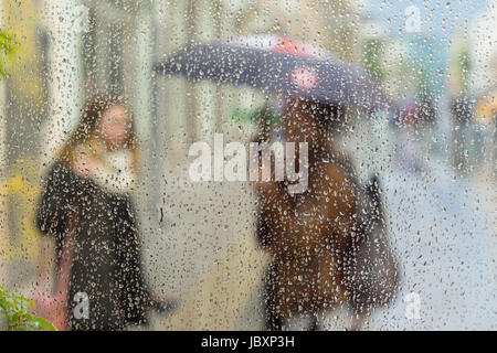 Abstract blurred silhouettes of people with umbrellas on rainy day in city, two girls seen through raindrops on - Stock Photo