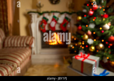 Out of focus background with living room decorated for Christmas with burning fireplace - Stock Photo
