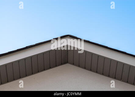 Top of residential house roof edge and siding against clear sky. - Stock Photo