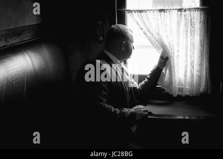 Monochrome portrait of elegant man sitting in train coupe and looking out of window - Stock Photo