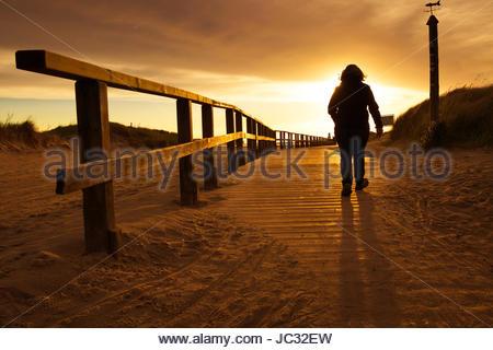 Wooden beach boardwalk woman walking on beach trail beach at sunset beach pathway woman german beach holiday travel - Stock Photo