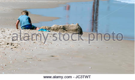 Young boy playing in the sand on the sea beach - Stock Photo