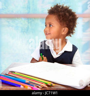 Portrait of cute little African preschooler on drawing lesson, painting with many colorful pencils, elementary education - Stock Photo