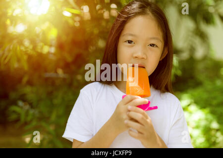 Happy Asian child eating popsicle ice cream during hot summer day. - Stock Photo