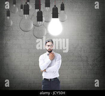 Businessman with glowing light bulb - Stock Photo