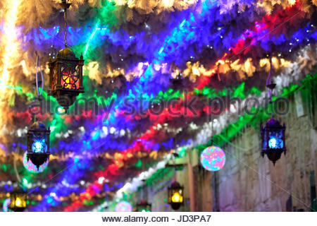 An alley decorated with festive lights during the Muslim holy month of Ramadan in the Muslim Quarter in the Old - Stock Photo