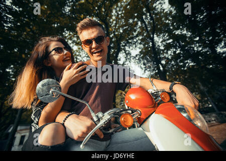 Young attractive couple of teenagers wears sunglasses on retro motorbike in park, hipster concept, 120FPS slowmotion - Stock Photo