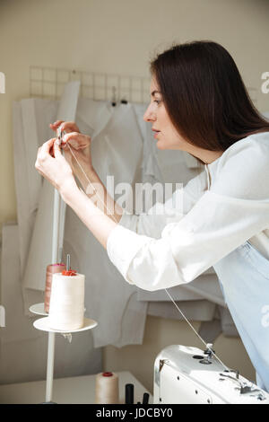 Side view of brunette seamstress in apron working with sewing machine in workshop - Stock Photo