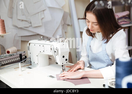 Image of brunette seamstress in apron working with sewing machine in workshop - Stock Photo