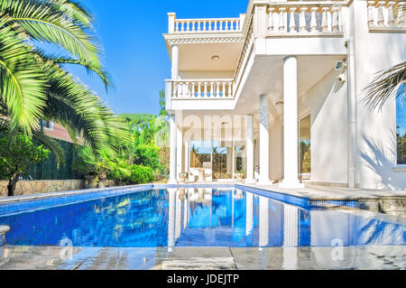 Luxury white house  with swimming pool. Luxury villa in classical style with columns.  Backyard with swimming pool - Stock Photo