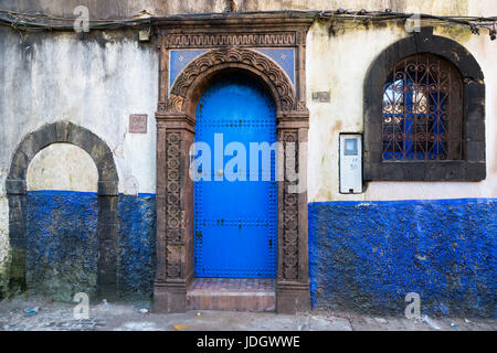 Windows and doorways of different shapes and colours on every house in the old town of Essaouira, Morocco - Stock Photo