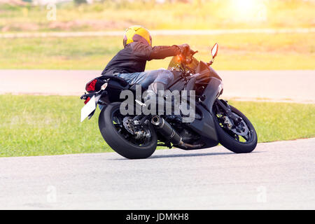 young man riding motorcycle in asphalt road curve wearing full safety suit - Stock Photo