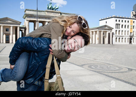 Man carrying girlfriend in town square - Stock Photo