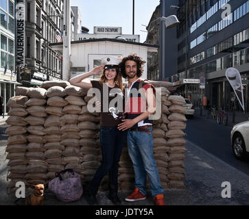 Couple smiling at Checkpoint Charlie - Stock Photo