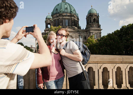 Man taking picture of couple - Stock Photo