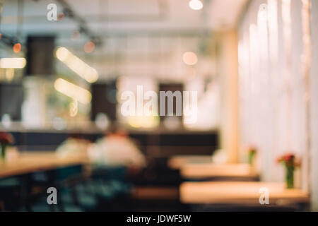 Blurred background of stylish cafe made in loft style with big windows and perfect luxury lightening. - Stock Photo