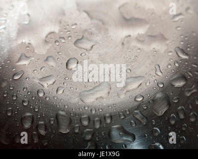Water droplets on a shiny metal surface - Stock Photo