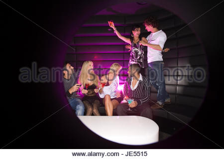 Young couple dancing in a nightclub with their friends having a drink - Stock Photo