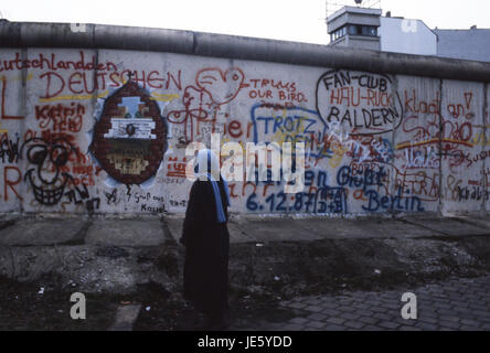 A lady reads the graffiti on the Berlin Wall, whilst East German boarder guards look on. Berlin 1987 - Stock Photo