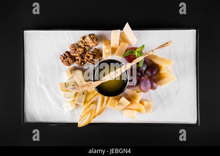 A large plate with a wide selection of snacks like grapes, cheese, walnuts, crackers on dark background. top view - Stock Photo