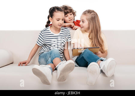 Group of cute friends using digital tablet while sitting on couch - Stock Photo