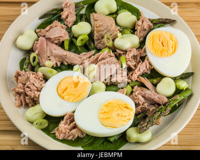 Tuna Fish Salad with Broad Beans Boiled Eggs and Asparagus On a Wooden Chopping Board - Stock Photo