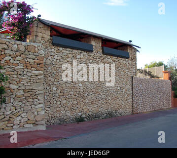 Wall of a garage, houses made of decorative natural stone - Stock Photo