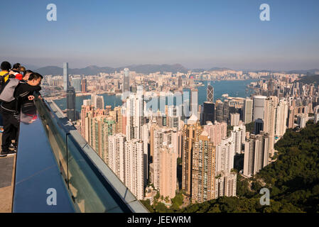 Horizontal view of people enjoying the view from up the Peak in Hong Kong, China. - Stock Photo