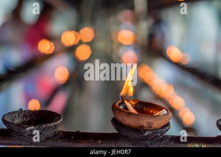 Coconut oil lamps in temple - Stock Photo