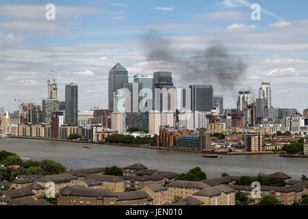 London, UK. 26th June, 2017. Black smoke rises over Canary Wharf buildings from a construction site fire in Wood - Stock Photo