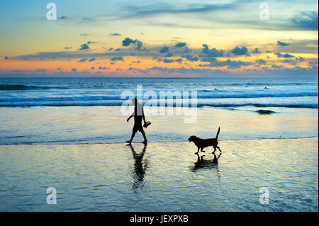 Silhouette of a man and dog walking on a beach at sunset. Bali island, Indonesia - Stock Photo